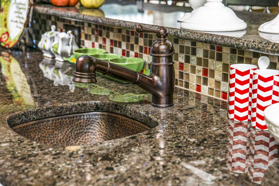 Rare Norwegian Granite Counters and Hammered Copper Bar Sink with Sprayer Faucet.