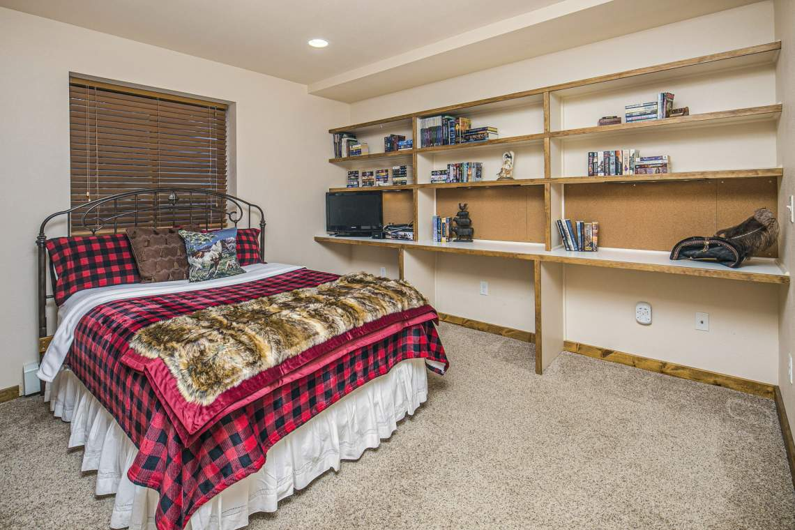 Basement Bedroom with Built In Shelves and Desk Area.