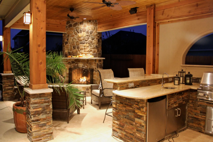 A Fireplace, plants and outdoor kitchen are all great for better backyard living spaces